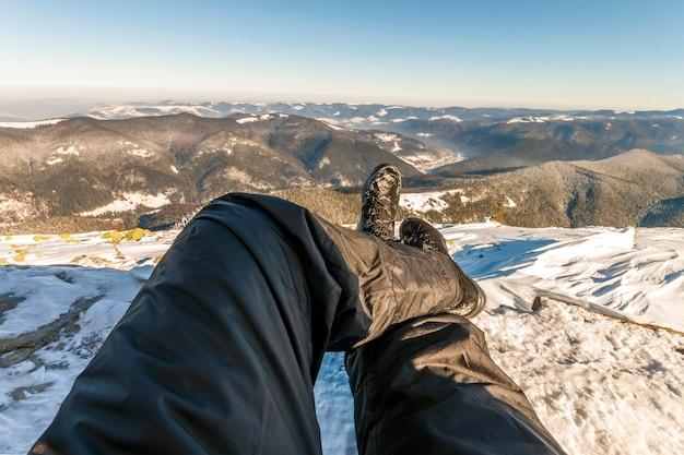 Piernas para hombre en zapatos de invierno contra el panorama sobre las montañas de los cárpatos. Foto Premium
