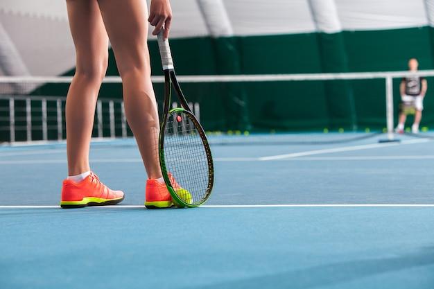 Piernas de joven en una cancha de tenis cerrada con pelota y raqueta Foto gratis
