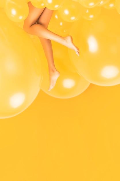 Piernas de mujer entre muchos globos amarillos Foto gratis
