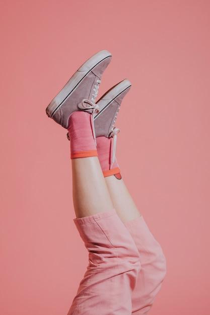 Piernas de mujer en pantalón rosa arriba en el aire. Foto gratis
