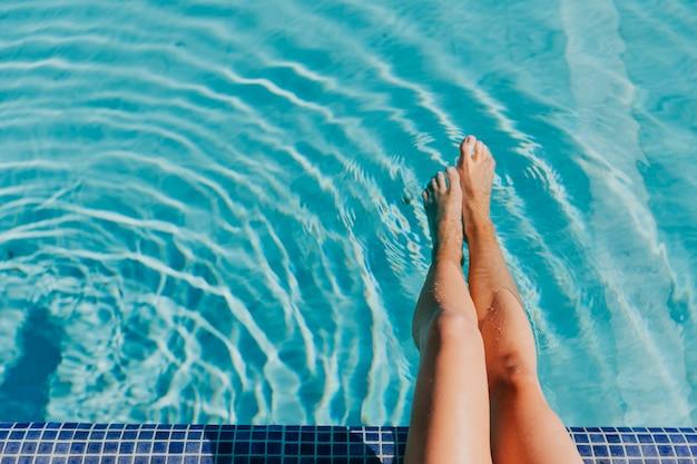 Piernas de mujer por piscina Foto gratis