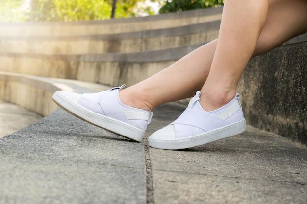 8976afd0 Piernas de mujer con zapatos blancos sentado deporte | Descargar ...