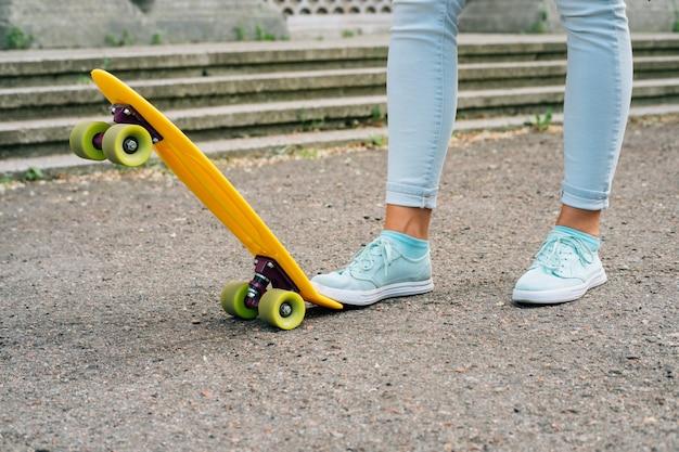 Piernas de las mujeres en jeans y zapatillas de pie junto al patín Foto Premium