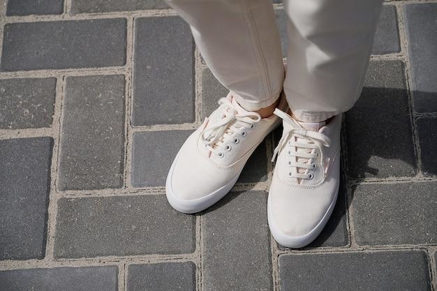 Piernas de la niña en nuevas zapatillas blancas y jeans Foto Premium