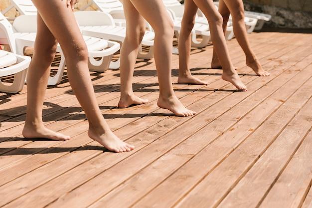 Piernas en el piso de madera en la piscina Foto gratis