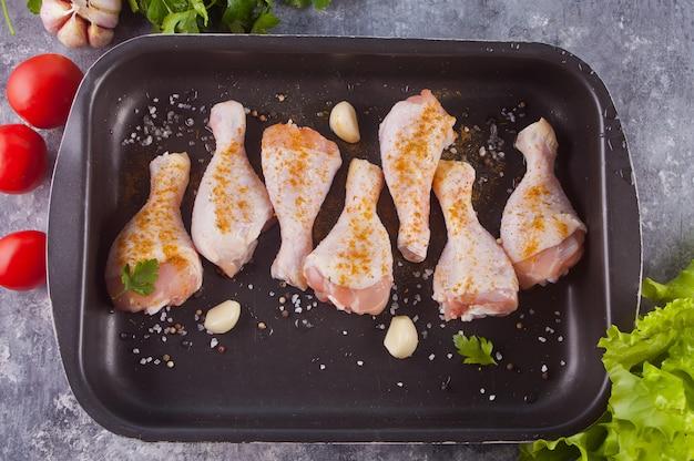 Piernas de pollo crudo en la sartén negra. Foto Premium