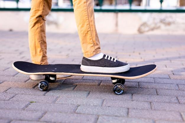 Las piernas del skater montando patineta en la calle de la ciudad Foto Premium