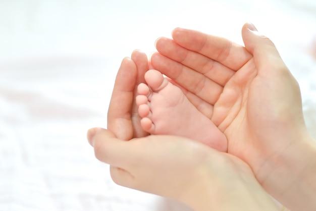 Pies del bebé en manos de la madre. Foto gratis