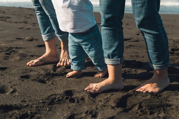 Pies de bebé y padres caminando en la costa de arena Foto gratis
