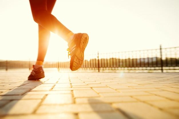 Pies de corredor corriendo en carretera closeup en zapato. mujer fitness amanecer jog entrenamiento bienestar concepto. Foto gratis