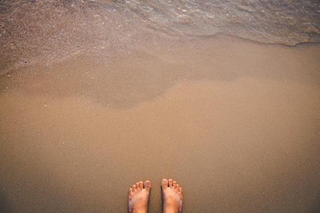 Pies descalzos en la playa de arena con ola Foto Premium