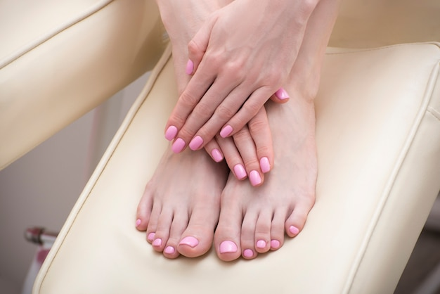 Pies femeninos y manos con una manicura rosa. salón de belleza. de cerca Foto Premium