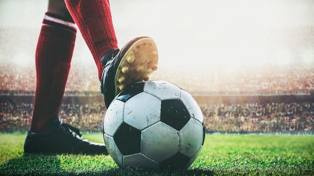Pies de jugador de fútbol pisa en balón de fútbol para el saque inicial en el estadio Foto Premium