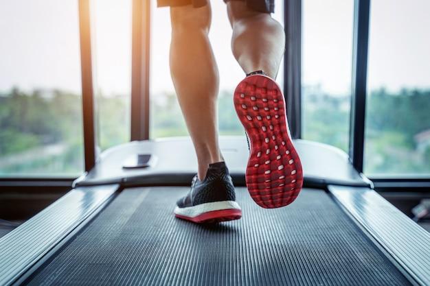 Pies masculinos en zapatillas corriendo en la cinta en el gimnasio. concepto de ejercicio. Foto gratis