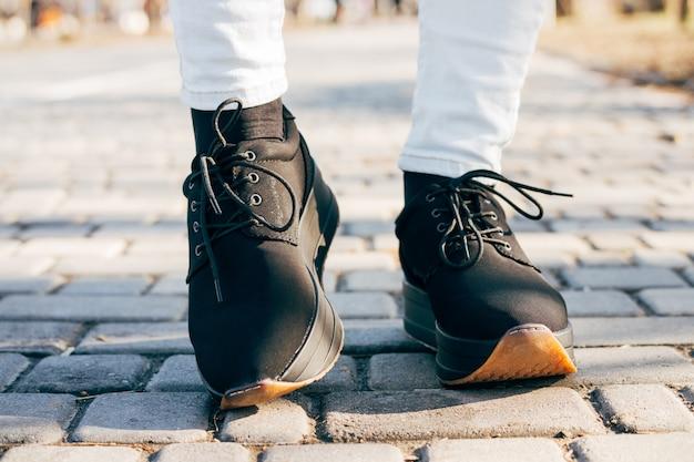Pies de mujeres en zapatos negros en la acera en un día soleado Foto Premium