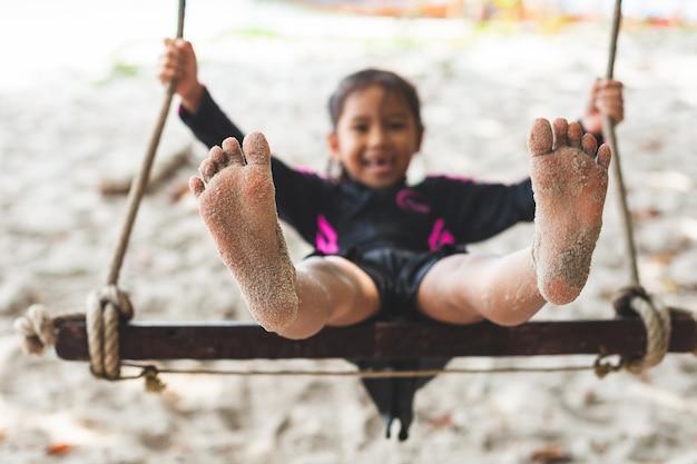 Pies de niño con arena mientras ella juega en un columpio en la playa cerca del mar en vacaciones de verano Foto Premium