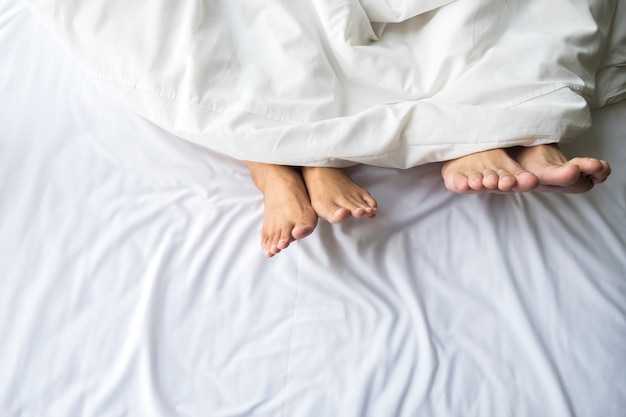 Pies de pareja en cama cómoda. Foto gratis