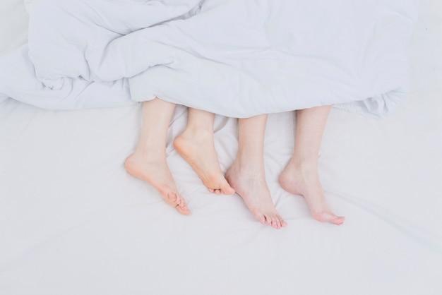 Pies de la pareja lesbiana fuera de la manta sobre la cama Foto gratis