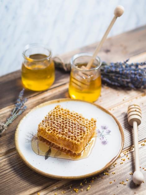 Pieza de panal en plato blanco con miel olla y lavanda sobre la mesa de madera Foto gratis