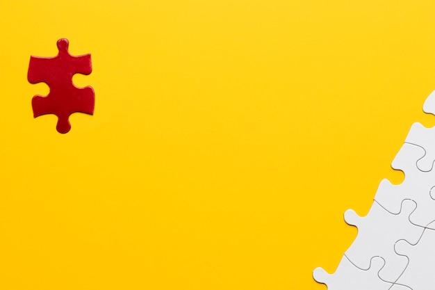 Pieza del rompecabezas rojo de pie por separado de la pieza del rompecabezas blanco sobre fondo amarillo Foto gratis