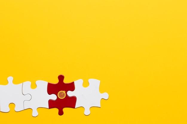 Pieza del rompecabezas rojo con el símbolo de la diana dispuesta con la pieza blanca sobre fondo amarillo Foto gratis