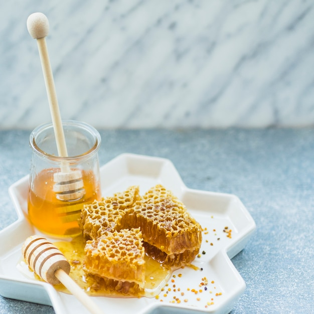 Piezas de panal y tarro de miel en bandeja floral Foto gratis