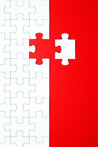 Piezas de un rompecabezas blanco sobre un fondo rojo separados Foto Premium