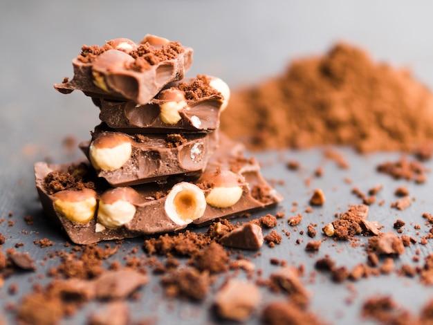 Pila de barras de chocolate y cacao en polvo. Foto gratis