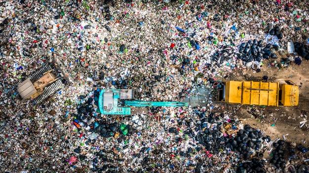 La pila de basura en un basurero o vertedero, los camiones de basura de vista aérea descargan la basura en un vertedero, el calentamiento global. Foto Premium