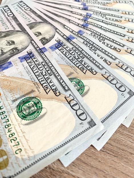 Pila de billetes de cien dólares en escritorio de madera Foto Premium