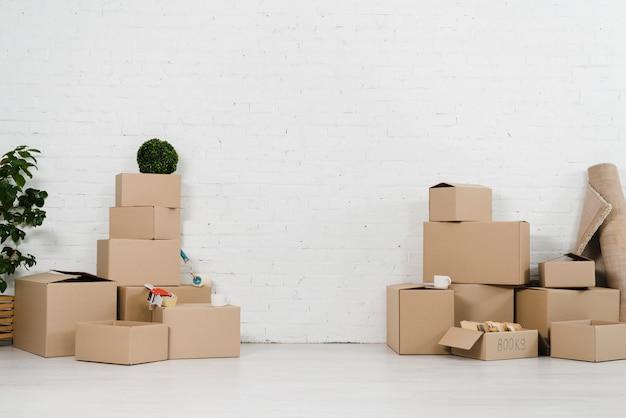 Pila de caja móvil en casa nueva contra la pared de ladrillo blanco Foto Premium