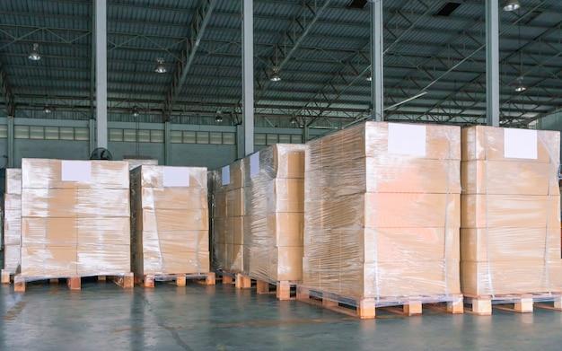 Pila de cajas de embalaje que envuelven plástico en paletas en el almacén de almacenamiento Foto Premium