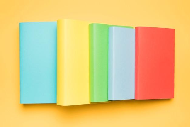 Pila de coloridos libros en blanco sobre fondo amarillo Foto gratis
