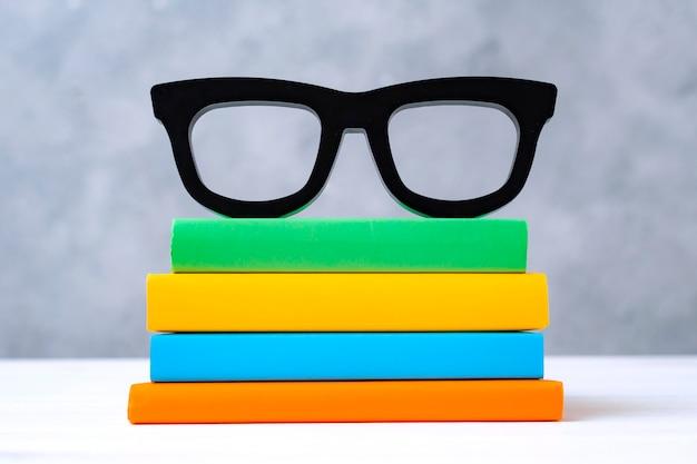 Pila de coloridos libros con gafas en una mesa de madera blanca contra una pared gris. el concepto de volver a la escuela, lectura, biblioteca, literatura, estudio, educación. Foto gratis