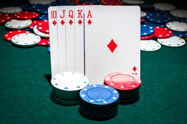 Pila de fichas de casino frente a naipes de escalera real Foto gratis