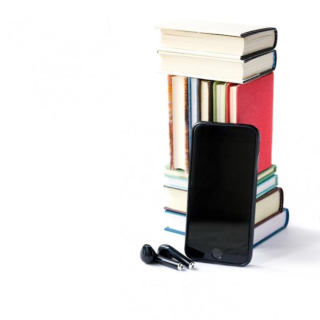 Pila de libros de colores, auriculares y teléfono móvil. Foto Premium