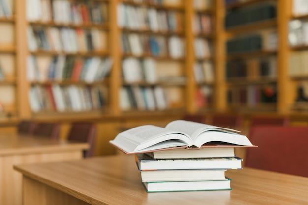 Pila de libros en el escritorio de la biblioteca Foto gratis