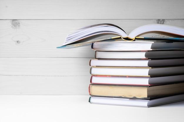 Una pila de libros en un fondo de madera. Foto Premium