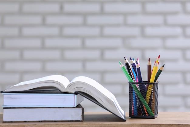 Pila de libros y lápices sobre el escritorio. Foto gratis