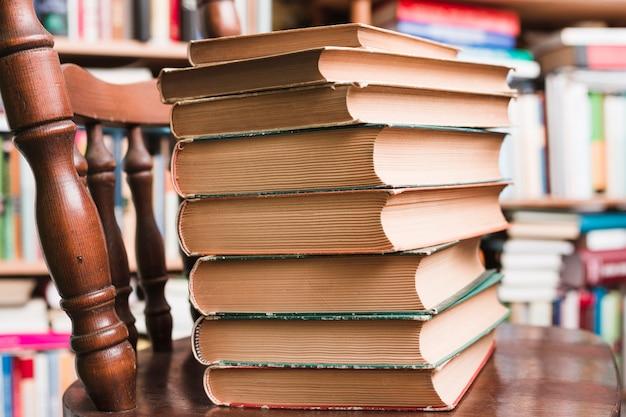 Pila de libros en una silla Foto gratis