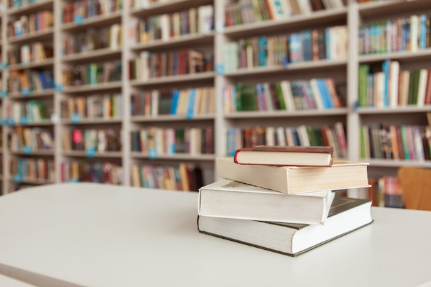 Pila de libros sobre la mesa en la biblioteca Foto Premium