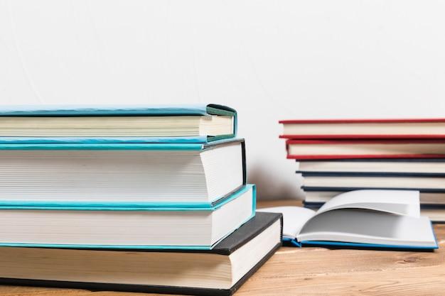 Pila de libros sobre mesa de madera minimalista. Foto gratis