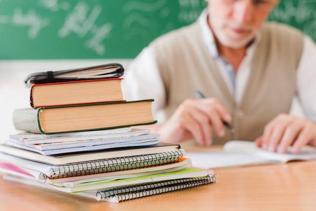 Pila de libros de texto dispuestos en el escritorio del profesor en la sala de conferencias Foto gratis