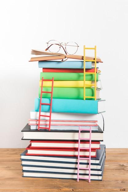 Pila de libros con vidrios y escaleras. Foto gratis