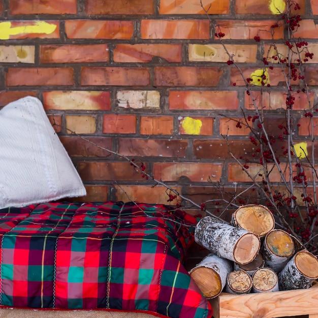 Una Pila De Madera De Abedul Cerca Del Sofá Con Una Manta