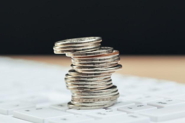 Pila de monedas y calculadora, idea conceptual para finanzas empresariales Foto Premium