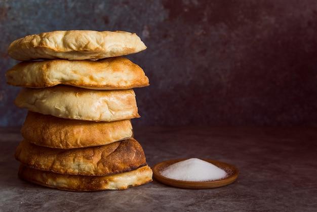 Pila de panes planos con sal vista frontal Foto gratis