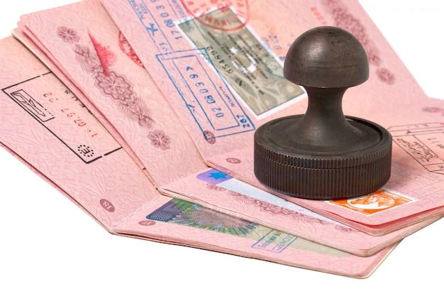 Una pila de pasaportes y sello aislado en blanco Foto Premium