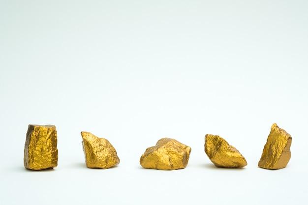 Una pila de pepitas de oro o mineral de oro sobre fondo blanco Foto Premium