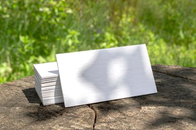 Pila de tarjetas de visita tipográficas en blanco acostado en un tocón escenario al aire libre con sombras florales Foto gratis